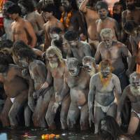 As millions arrive for India's Kumbh Mela festival, tens of thousands of holy men, faithful take dip in river