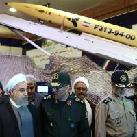 Iranian President Hassan Rouhani (second from left) and Defense Minister Hossein Dehghan (center) unveil the surface-to-surface Fateh-313 missile in Tehran on Saturday. | AFP-JIJI