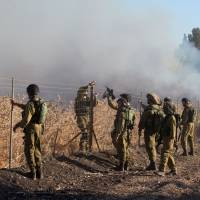 Israeli soldiers stand next to smoke from a fire caused by a rocket attack in northern Israel, near the Lebanese border, Thursday. Rockets that struck an northern Israeli village near the Lebanese border on Thursday, causing no casualties, were launched from the Syrian Golan Heights, the Israeli army said. | JIJIPIX / REUTERS