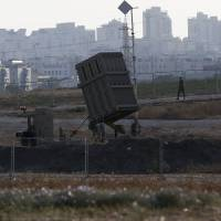 An Israeli soldier walks past an 'Iron Dome' battery, a short-range missile defense system designed to intercept and destroy incoming short-range rockets and artillery shells, on Thursday in the city of Ashdod. | AFP-JIJI