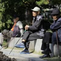 Elderly men sit on benches at Tapgol Park in Seoul. South Korean government efforts to stimulate consumer spending are being challenged by the swelling ranks of seniors. Average life expectancy is above 80 and older people are trying to save more and spend less during their ever-longer years of retirement. | BLOOMBERG