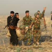 A wounded Kurdish officer is taken for treatment, during a military operation to regain control of some villages from Islamic State group fighters south of Kirkuk, Iraq, Wednesday. | AP