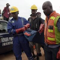 Officials of the National Emergency Management Agency (NEMA) and the paramilitary Nigeria Security and Civil Defence corps (NSCDC) carry the body of a dead passenger from a helicopter operated by the US-based Bristow Group that crashed into a lagoon at the Oworonshoki district of Lagos on Wednesday.   AFP-JIJI