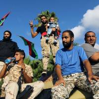 Libyan supporters and troops loyal to Khalifa Haftar, a retired general and former chief of staff for Moammer Gadhafi, sit on an amored personnel carrier (APC) during a demonstration calling on the international community to arm the Libyan army on Friday in the eastern Libyan city of Benghazi. The Tobruk-based government (recognized by the international community) said in a statement that world powers were using 'double standards' by fighting Islamic State in Syria and Iraq and 'turning a blind eye' to the presence of the jihadis in Libya.   AFP-JIJI