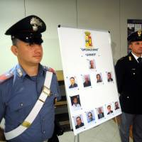 An Italian Carabinieri paramilitary police officer and a police officer stand next to mug shots of 11 men suspected of helping Matteo Messina Denaro during a press conference in Palermo, Italy, Monday Italian investigators say they've discovered how the No. 1 Cosa Nostra fugitive communicates with henchmen using written messages buried in dirt or hidden under boulders on Sicilian sheep ranches: in predawn raids Monday in western Sicily, police arrested 11 men suspected of helping Denaro stay in command despite being on the run since 1993. | AP