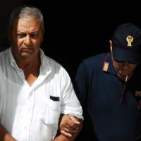 An Italian police officer takes into custody Michele Gucciardi, one of the 11 men suspected of helping No. 1 Cosa Nostra fugitive Matteo Messina Denaro, in Palermo, Sicily, Monday. | AP
