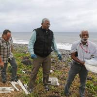 A Malaysian expert (center) looks for debris from Malaysia Airlines Flight 370 on a beach in Saint Andre, on the French territory of Reunion Island, on Tuesday. | AFP-JIJI