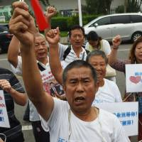 Relatives of passengers aboard Malaysia Airlines Flight 370 chant slogans while waiting to meet with Malaysian officials, outside an office in Beijing on Friday. | AFP-JIJI