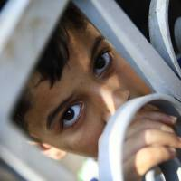 Abdulrahman, 10, last name not given, a Palestinian refugee who was living in Damascus, stands behind the locked gates of a center where migrants are held until they are properly registered, on the grounds of the hospital in the island of Leros, Greece, Monday. This Greek island that was once a place of exile for political prisoners has become one of the country's most welcoming communities for migrants fleeing chaos and war, thanks to a dedicated grass-roots volunteer network and tourists interrupting their vacations to provide what help they can. | AP