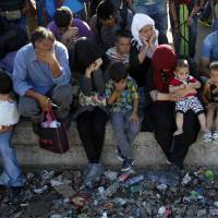 Migrants wait for a train heading toward Serbia at the railway station in the southern Macedonian town of Gevgelija on Tuesday5. Record numbers of migrants from countries like Syria, Iraq and Afghanistan uses the so-called Balkan route that passes trough Macedonia. | AP