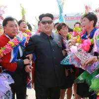 North Korean leader Kim Jong Un greets the country's women's soccer team as they arrive at Pyongyang International Airport on Monday after winning the 2015 EAFF East Asian Cup. | REUTERS