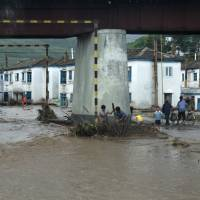 Residents attempt to clear flood debris from under a bridge in the city of Rajin, in North Korea, in this picture taken Saturday by a recent visitor.   REUTERS