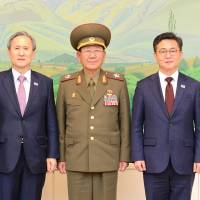 South Korean National Security Adviser Kim Kwan-jin (second from left) and Unification Minister Hong Yong-pyo (right) pose with senior North Korean Workers' Party official Kim Yang Gon (left) and Hwang Pyong-so, the top military aide to North Korean leader Kim Jong Un, after their talks at the truce village of Panmunjom on Tuesday. | REUTERS