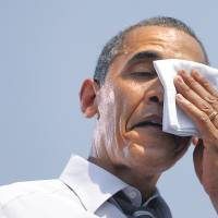 President Barack Obama wipes sweat from his face during a campaign event in Ames, Iowa in August 2012. The Obama administration is set to issue rules Monday to cut carbon emissions from U.S. power plants. | AP