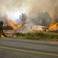 Firefighters flee as the Twisp River fire advances unexpectedly near Twisp, Washington Thursday. Crews battling a flurry of wildfires raging unchecked in the Pacific Northwest braced on Thursday for high winds forecast in the region a day after three firefighters were killed and four others were injured in Washington state. | REUTERS