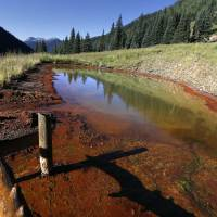 An abandoned mine wastewater pond is vivid with the colors of minerals, chemicals and vegetation, high in the San Juan Mountains north of Silverton, southwestern Colorado, Friday. The mines that settlers built in the booms of the 19th century are an ever-present part of the landscape in this mineral-rich part of Colorado.   AP