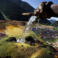 Hillside drainage water flows from a pipe into an abandoned mine site vivid with the colors of minerals, chemicals and vegetation, high in the San Juan Mountains north of Silverton, Colorado, Friday.   AP