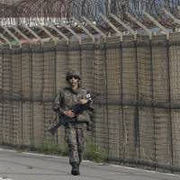 A South Korean soldier walks along wire fences on Unification Bridge, which leads to the demilitarized zone, near the border village of Panmunjom on Saturday. | AP