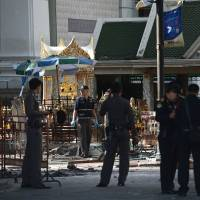 Policemen stand at the cordoned-off site of a bomb blast at the popular Erawan Shrine in the heart of Bangkok's tourist and commercial center on Tuesday. The death toll from a bomb blast in the Thai capital rose to 21 on Tuesday with 123 wounded, police said, adding that seven tourists, from China, Hong Kong, Malaysia and Singapore, among those killed in the attack. | AFP-JIJI