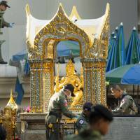 Police investigators work near the statue of Phra Phrom, which is the Thai interpretation of the Hindu god Brahma, at the Erawan Shrine the morning after an explosion in Bangkok Tuesday. | AP