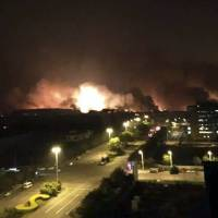 In this photo released by Xinhua News Agency, smoke and fire erupt into the night sky after an explosion in the Binhai New Area in north China's Tianjin Municipality on Thursday. | YUE YUEWEI / XINHUA VIA AP