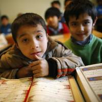 Uighur refugee boys read the Quran where they are housed in a gated complex in the central city of Kayseri, Turkey, in February. Thousands of members of China's Turkic language-speaking Muslim ethnic minority have reached Turkey, mostly since last year, infuriating Beijing, which accuses Ankara of helping its citizens flee unlawfully.   REUTERS