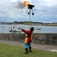 "Russel Erwood, also known as town jester Erwyd le Fol, balances a blazing barbecue on a wooden pole, a stunt known as ""The Burning Brushes of Beelzebub,"" after his naming ceremony in Conwy, Wales, on Sunday. 