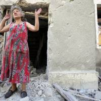 A woman reacts in front of her house destroyed as a result of shelling between Ukrainian forces and pro-Russian separatists on Monday in Golmovsky village, Donetsk region. Ukraine on Monday reported repelling a rare tank assault by pro-Russian rebels that threatened to usher in a dangerous escalation to the 16-month war. | AFP-JIJI