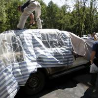 Members of the Organization for Security and Cooperation in Europe work near an OSCE car, which was burned overnight, near its office in Donetsk, Ukraine, Sunday. Four OSCE armored vehicles were destroyed overnight in an arson attack at the OSCE Special Monitoring Mission (SMM) to Ukraine residence, OSCE said on its Twitter feed. | REUTERS