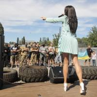 An actress sings for servicemen from the Azov volunteer battalion during a Monday ceremony in Kiev before they are sent to eastern Ukraine.   AP