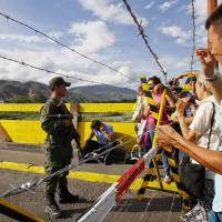 Venezuela closes Colombia border crossing, sends troops after attack on soldiers