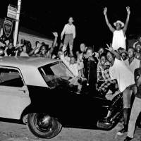 Demonstrators push against a police car on Aug. 12, 1965, after rioting erupted in the Watts district of Los Angeles. | AP