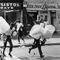 Looters carry lamps out of a store on Aug. 13, 1965, during the rioting that enveloped the Watts district of Los Angeles. | AP