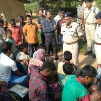 Indian police talk to villagers after five women were killed after being accused of practicing witchcraft in Kanjia village in eastern Jharkhand state on Saturday. | AFP-JIJI