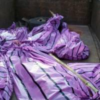 The bodies of five women killed by villagers who accused them of practicing witchcraft lay in plastic bags in Kanjia village in India's eastern Jharkhand state on Saturday. | AFP-JIJI