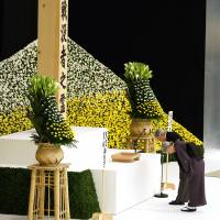 Japan's Emperor Akihito and Empress Michiko bow before the main altar decorated with huge bank of chrysanthemums during a memorial service at Tokyo's Nippon Budokan martial arts hall.   AP