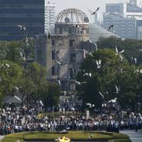 Doves fly over Peace Memorial Park, with the Atomic Bomb Dome in the background, during the annual ceremony in Hiroshima on Thursday.   REUTERS