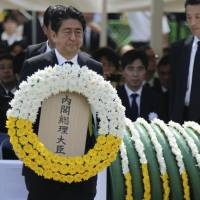 Prime Minister Shinzo Abe holds a wreath during a ceremony to mark the 70th anniversary of the atomic bombing of Nagasaki in the city Sunday. | AP