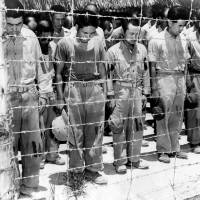 Japanese prisoners of war on Guam listen to a radio broadcast as Emperor Hirohito announces Japan's surrender in World War II  on Aug. 15, 1945. | KYODO