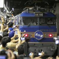 Train lovers gather to see the last 'blue train' long-distance sleeper in service arrive at Tokyo's Ueno Station from Sapporo on Sunday. It completed its final run nearly 60 years after debuting in 1958. | KYODO