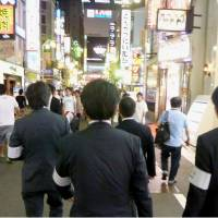 Lawyers from the Tokyo Bar Association patrol the Kabukicho entertainment district in Shinjuku Ward, Tokyo, July 17 as part of their efforts to eradicate 'bottakuri' rip-offs at bars and nightclubs. | KYODO