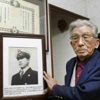 Toichi Nakatani holds a picture of his brother, Sakataro, in Osaka in March. Sakataro died in 1950 while engaged in a secret mission to remove underwater mines off Wonsan, in North Korea, during the Korean War. | KYODO