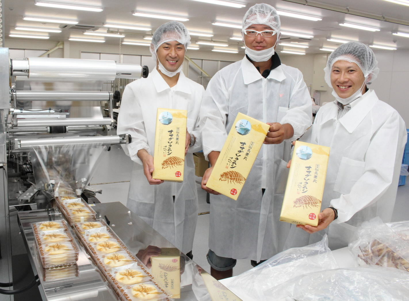 Kazutaka Hasegawa (center), a deep-sea fisherman, holds a package of giant isopod crackers at a production line in Fujieda, Shizuoka Prefecture. | CHUNICHI SHIMBUN