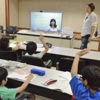 Children take an online class at a town hall in Kamikatsu, Tokushima Prefecture, in July. | KYODO