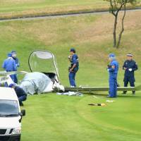 Investigators inspect an ultra-light plane that crashed into a golf course earlier on Sunday in Tsukuba, Ibaraki Prefecture. | KYODO