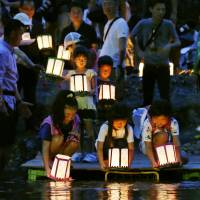 Children float paper lanterns on the Kanna River in the village of Ueno, Gunma Prefecture, on Tuesday in memory of the victims of JAL Flight 123, a 747 that crashed nearby 30 years ago.   KYODO