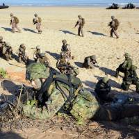 Ground Self-Defense Force soldiers and U.S. Marines conduct a joint drill at Fog Bay in northern Australia on July 11. | KYODO