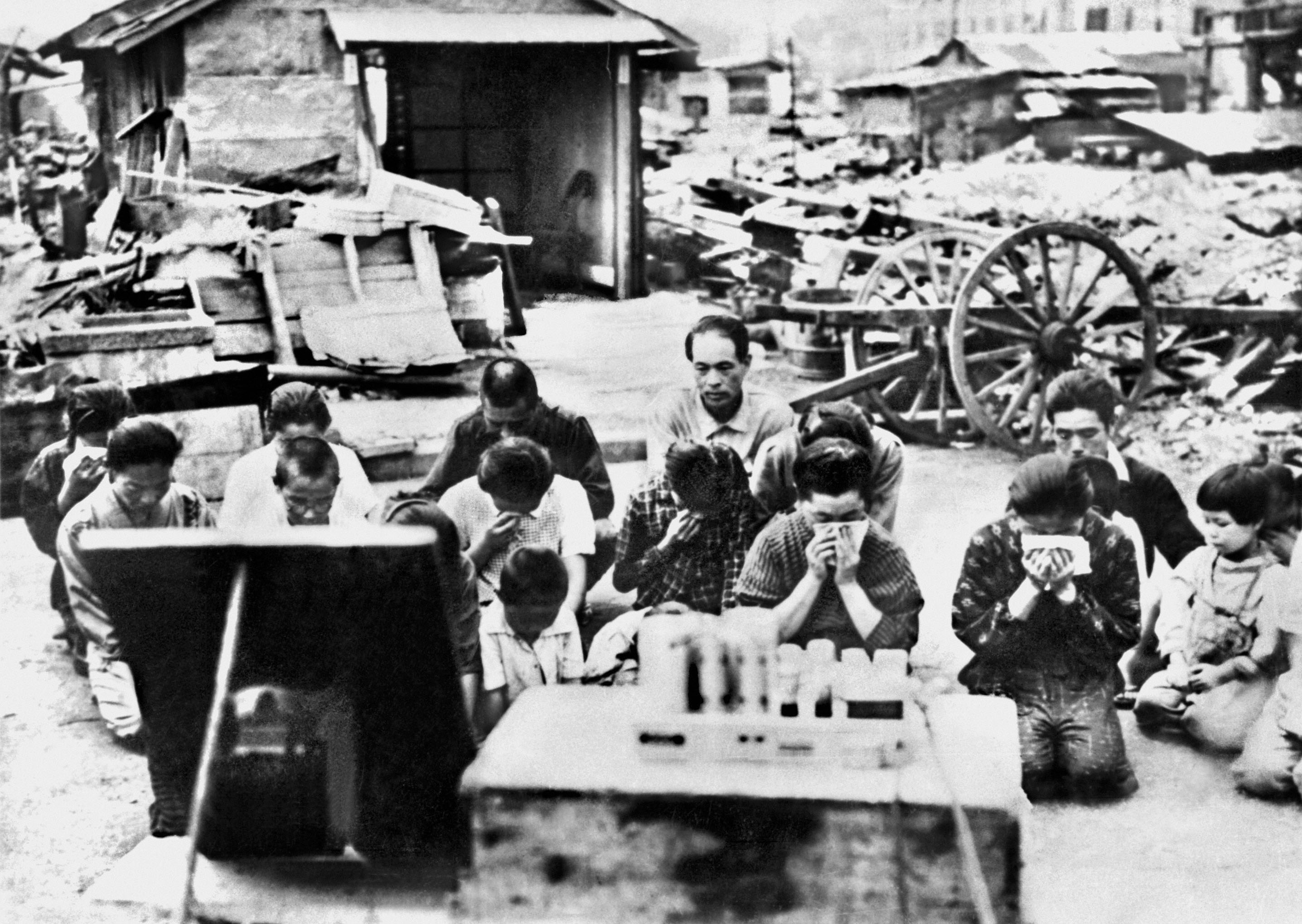 People shed tears as they kneel down and listen to Emperor Hirohito's broadcast announcing Japan's surrender on Aug. 15, 1945, in this unspecified location. | KYODO