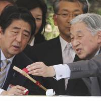 Emperor Akihito and Prime Minister Shinzo Abe touch a kyujyo racket and ball for dakyu, an equestrian sport similar to polo, during demonstrations at the Imperial Palace in Tokyo in May. | AP