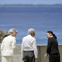 Emperor Akihito and Empress Michiko listen to an aide during their April visit to Peleliu Island, Palau, to commemorate Japanese and American soldiers who lost their lives there during World War II.   KYODO